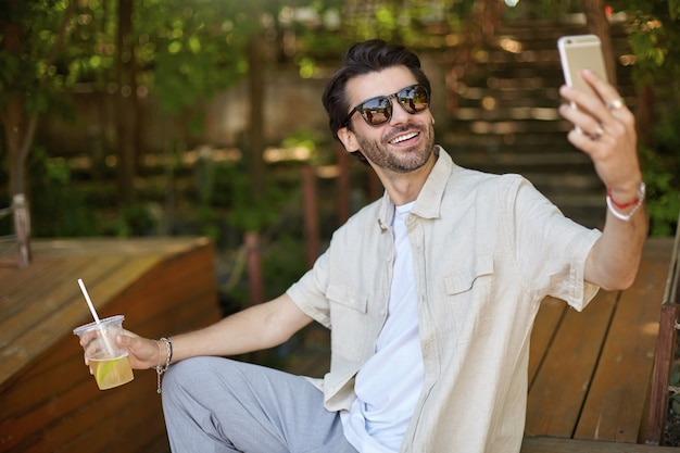 Outdoor photo of young dark haired male in sunglasses and beige shirt sitting on bench in city park, looking cheerfully and making selfie with his smartphone
