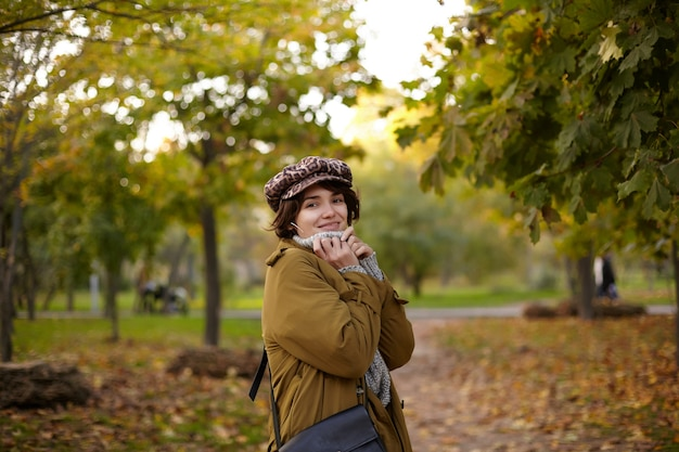 Outdoor photo of young positive attractive brown haired woman keeping hands on her poloneck while looking  with charming smile, walking over city park