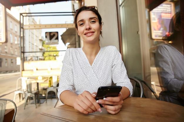 Foto all'aperto di giovane donna dai capelli piuttosto scura con acconciatura casual tenendo il cellulare in mano e guardando piacevolmente con un sorriso leggero
