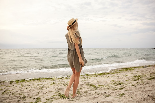 Outdoor photo of young slim long haired blonde woman dressed in green summer dress standing with her back over beach background and keeping hand on her hat