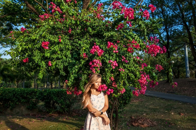 Outdoor photo of young woman with blooming bougainvillea