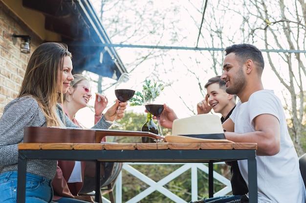 Наружная фотография молодых людей, подающих тосты с бокалами на крыше - пара друзей, наслаждающихся едой на открытом воздухе.