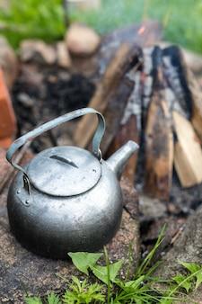 Чайник для пикника на открытом воздухе с винтажным оттенком у костра.