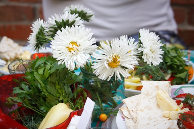 Outdoor picnic, served disposable plate with snacks, a glass of vodka and a bouquet of white asters