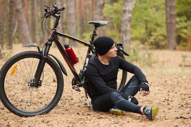 Outdoor picture of athletic strong sportsman wearing black shirt, sport pants, hat and trainers, leaning on bicycle, looking far ahead