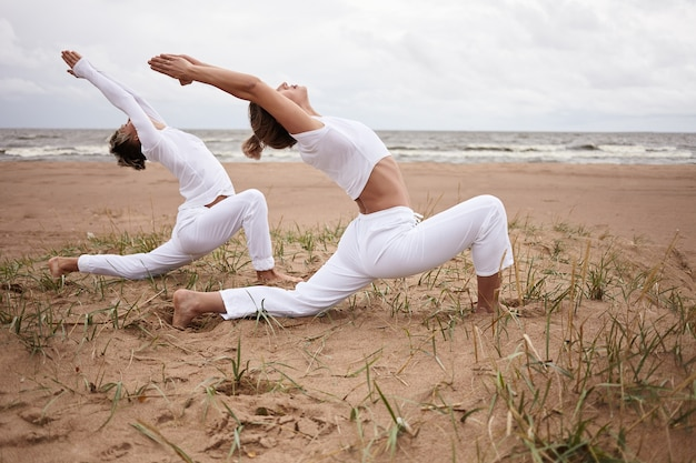 Outdoor picture of beautiful sporty european female and her teenage athletic son practicing hatha yoga by the sea together, standing in virabhadrasana ii or warrior 2 pose on deserted sandy beach
