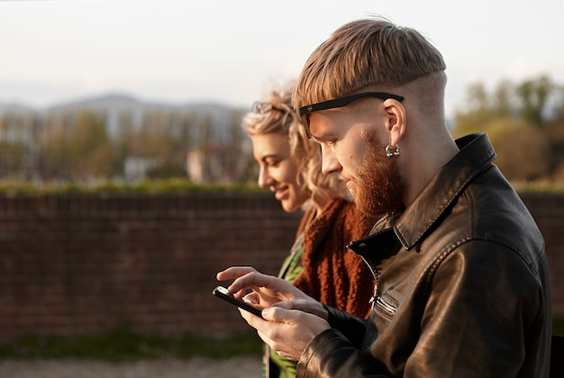 Outdoor picture of fashionable red haired young man wearing earring and biker jacket using mobile phone while walking together with beautiful blonde girl. first date, romance and technology concept