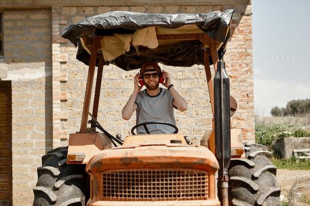 Foto all'aperto di bello allegro giovane barbuto agricoltore indossando occhiali da sole