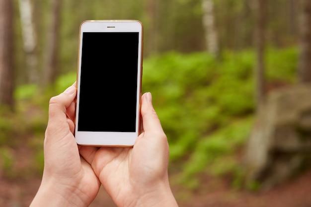 スマートフォンを持っている手の屋外の写真がオフになっている、上げている、オンにしようとしている、接続を見つけようとしている、新しいデバイスを使用している、空白の画面を持っている、自然のモバイル