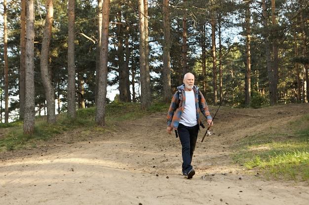 낚싯대가 숲 속 길을 따라가는 슬픈 노인 수염 난 남자의 야외 사진, 그가 전혀 물고기를 잡지 않았기 때문에 실망한 표정. 낚시터에서 활동 및 레크리에이션