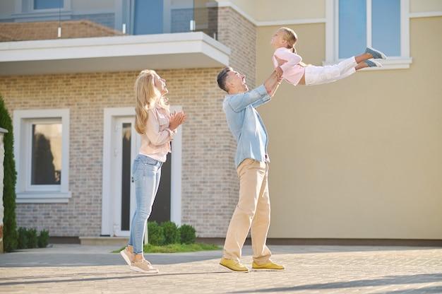 야외 놀이. 돌보는 사랑스러운 아빠는 기뻐하는 작은 딸을 팔짱을 끼고 키우고 웃는 엄마는 좋은 날 집 근처를 걷고 있다