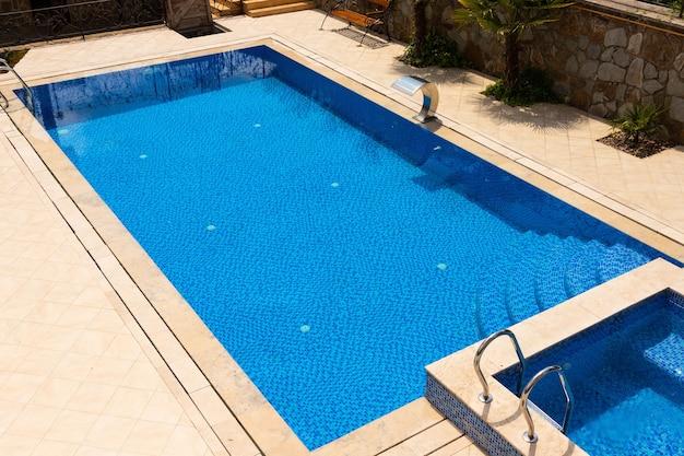 Открытый бассейн с голубой водой без людей.