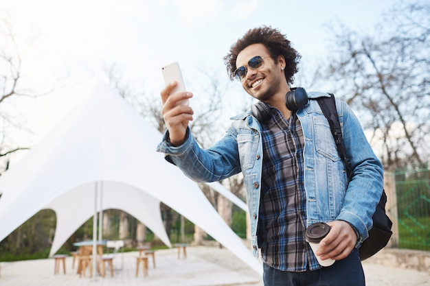 Outdoor portarit of happy sincere african american man in stylish glasses and denim coat, holding cup of coffee and taking photo on smartphone while smiling broadly during walk in park.