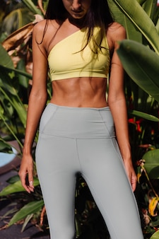 Outdoor portraif of fit slim sporty tanned pretty caucasian woman in sport yellow top and leggings over tropical plants
