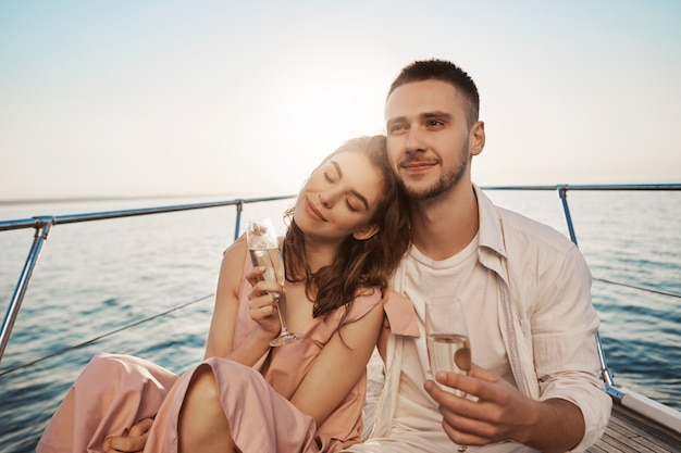 Outdoor portrait of adult happy male and female in love, celebrating their engagement on yacht, holding glass of champagne and hugging. boyfriend just told about things he likes in her