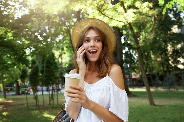 Il ritratto all'aperto della giovane donna attraente stupita indossa un cappello estivo alla moda e un vestito bianco, si sente felice e sorpreso, cammina nel parco con una tazza di caffè da asporto e parla al cellulare