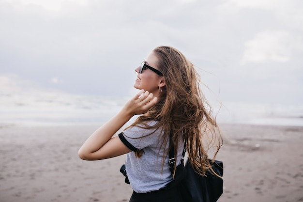 Outdoor portrait of amazing girl with long dark hair expressing happiness during walk around beach. inspired female model in gray t-shirt spending time near sea in cloudy day.