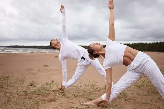 Outdoor portrait of attractive woman and young male with athletic bodies both dressed in white outfits, practicing yoga at seaside during retreat, doing utthita trikonasana or extended triangle pose