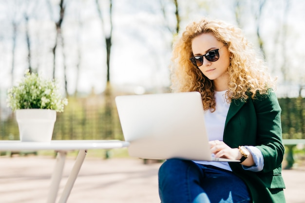 Outdoor portrait of attractive young woman with fluffy blonde hair wearing sunglasses, jeans and green jacket holding laptop computer
