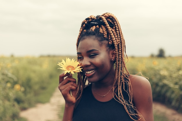 Outdoor portrait of beautiful african american girl in a field of yellow flowers