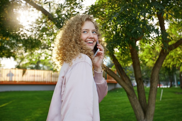 Outdoor portrait of beautiful attractive charming curly hair young woman passes by, speaking with someone on phone