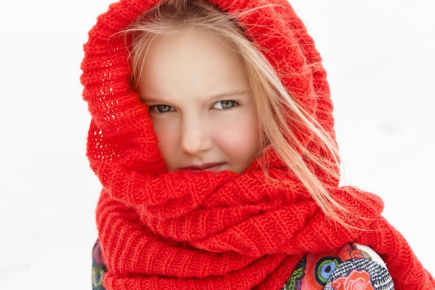 Ritratto all'aperto di bella bambina caucasica bionda avvolta in sciarpa rossa calda