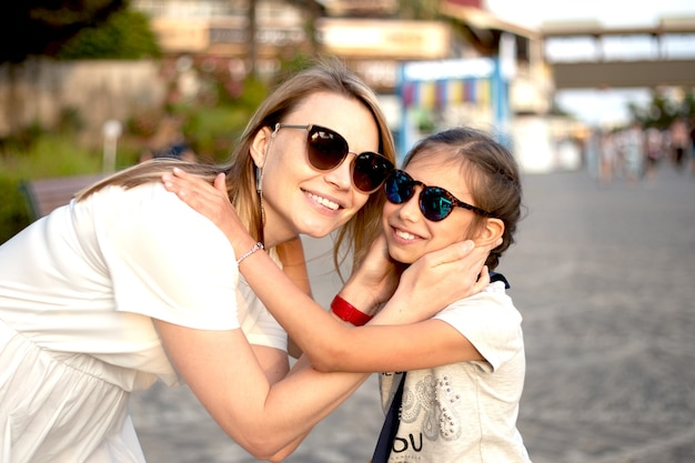 Outdoor portrait of beautiful blonde mother and her cute child. small girl hugging her mom on the beach.