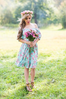 Outdoor portrait of a beautiful blonde woman. attractive happy girl in a field with bouquet of flowers.