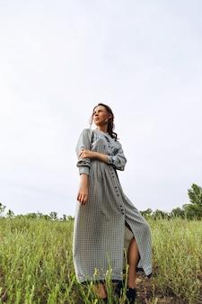 Outdoor portrait of a beautiful brunette woman in blue dress in the field