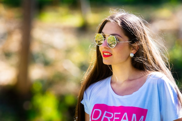 Outdoor portrait of beautiful, emotional, young woman in sunglasses.