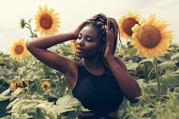 Outdoor portrait of beautiful happy mixed race african american girl teenager female young woman in a field of yellow flowers at sunset golden evening sunshine Premium Photo