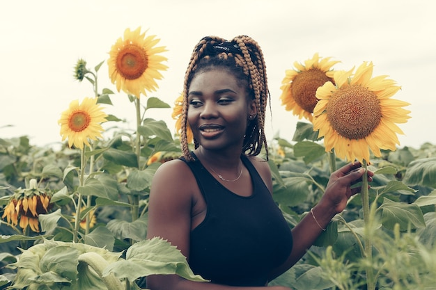 Outdoor portrait of beautiful happy mixed race african american woman in a field of yellow flowers at sunset golden evening sunshine