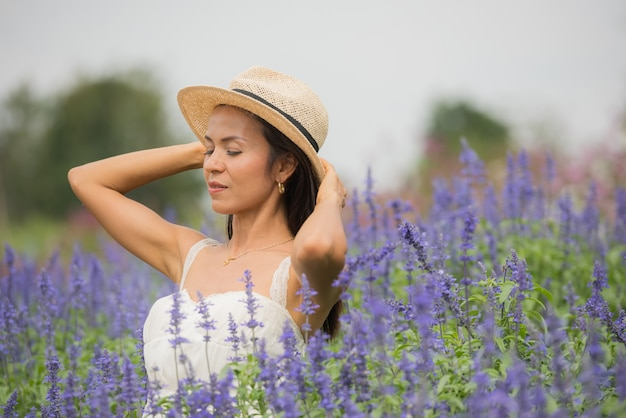 Outdoor portrait of a beautiful middle aged asia woman. attractive girl in a field with flowers