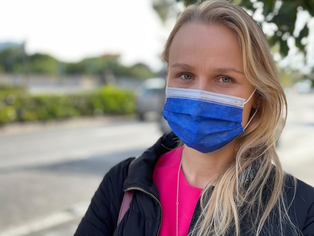 Outdoor portrait of a blond woman wearing a medical mask. life with covid-19 restrictions