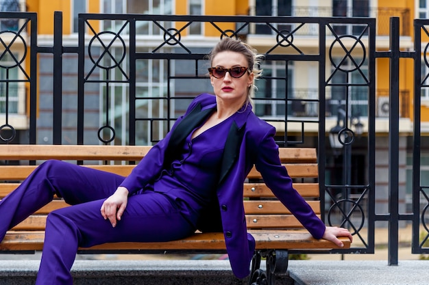 An outdoor portrait of a businesswoman in a colorful pantsuit. the model poses on the wooden bench against the big glass office.