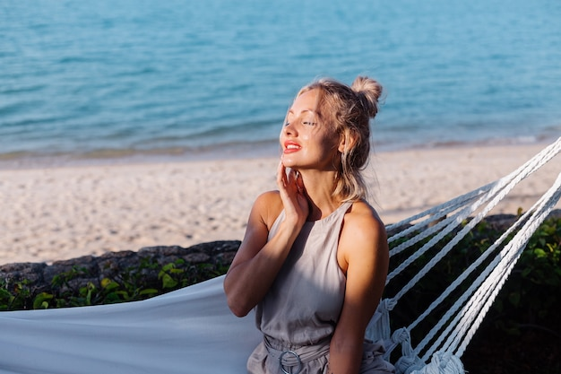 Outdoor portrait of caucasian woman in classic jumpsuit with red lipstick by hammock on vacation outside villa hotel, sea side