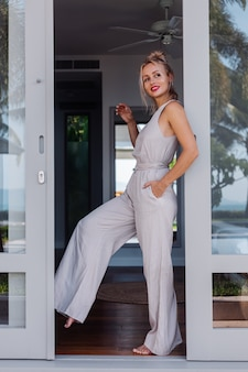 Outdoor portrait of caucasian woman in classic jumpsuit with red lipstick on vacation outside villa hotel