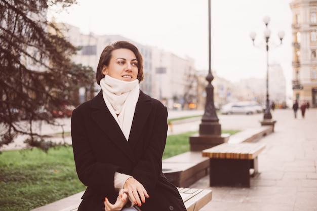 Outdoor portrait of caucasian woman wearing black winter coat and scarf sitting on bench, city on background
