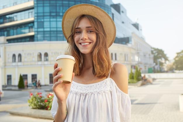 Ritratto all'aperto di allegra attraente giovane donna indossa un cappello elegante, si sente felice, in piedi e beve caffè da asporto in città in estate