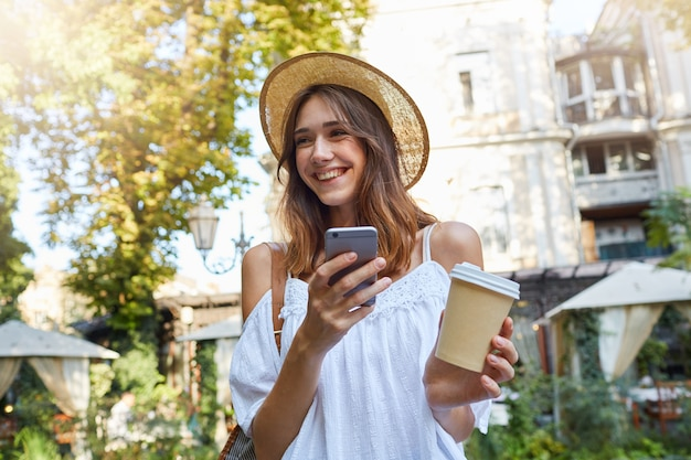 Outdoor portrait of cheerful pretty young woman wears stylish summer hat and white dress, feels happy, using cell phone, drinking takeaway coffee and laughing in old city