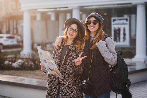 Outdoor portrait of cheerful woman with black backpack and camera embracing her friend and smiling. joyful young woman in elegant hat holding city map and making peace sign laughing with sister.
