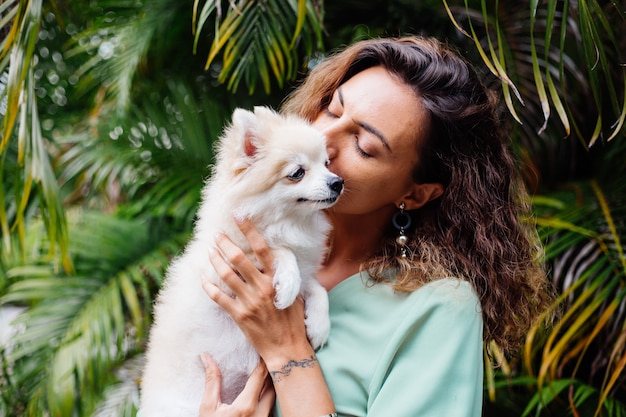 Outdoor portrait of curly european tanned woman holds happy pet dog pomeranian spitz