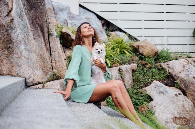 Il ritratto all'aperto della donna abbronzata europea riccia tiene lo spitz pomeranian del cane da compagnia felice