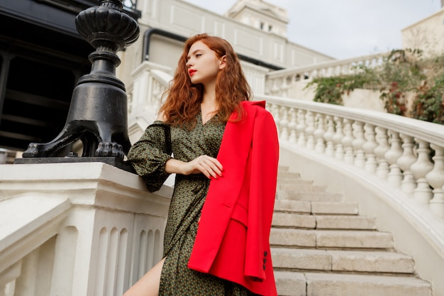 Outdoor portrait of elegant ginger woman in green dress and red jacket standing on stairs near bridge