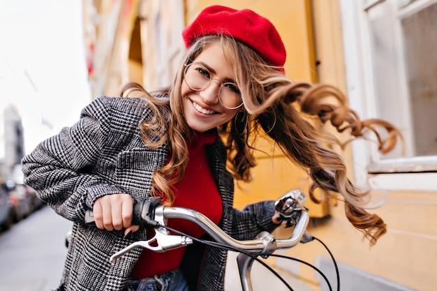 Ritratto all'aperto di signora riccia emotiva che esplora la città in bicicletta
