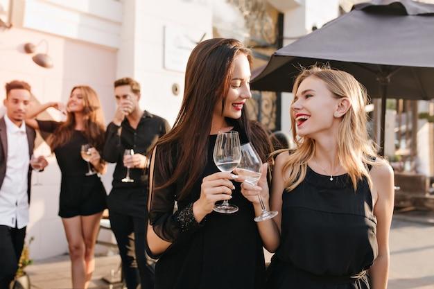 Ritratto all'aperto di donne castane entusiaste in abiti neri in posa