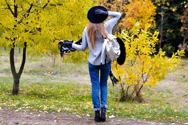 Outdoor portrait of excited girl wears trendy broad-brim and standing in confident pose. attractive young woman in glasses posing on autumn nature background.