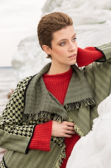 Outdoor portrait of fashion model with short haircut in front of the icy rock wearing green jacket with red jumper and looking aside.