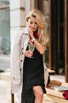 Outdoor portrait of fashionable female model in pleated dress drinks champagne and looking down. joyful blonde girl in beige trench coat holding glass of wine while standing on the street in cold day.