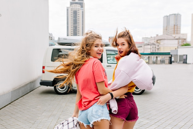 Outdoor portrait from back of ecstatic girls in denim shorts posing with hair waving by wind